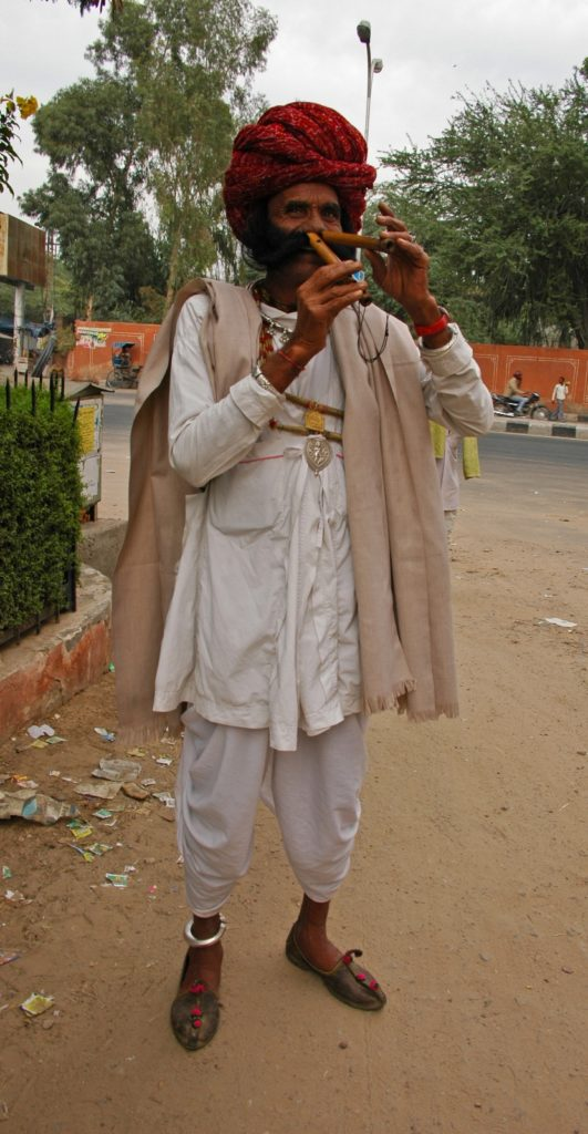 Jaipur - Street musician playing on flute with his nose