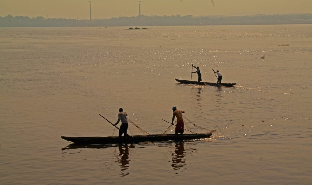 Kinshasa - fishermen on the Congo river. Brazzaville in the background
